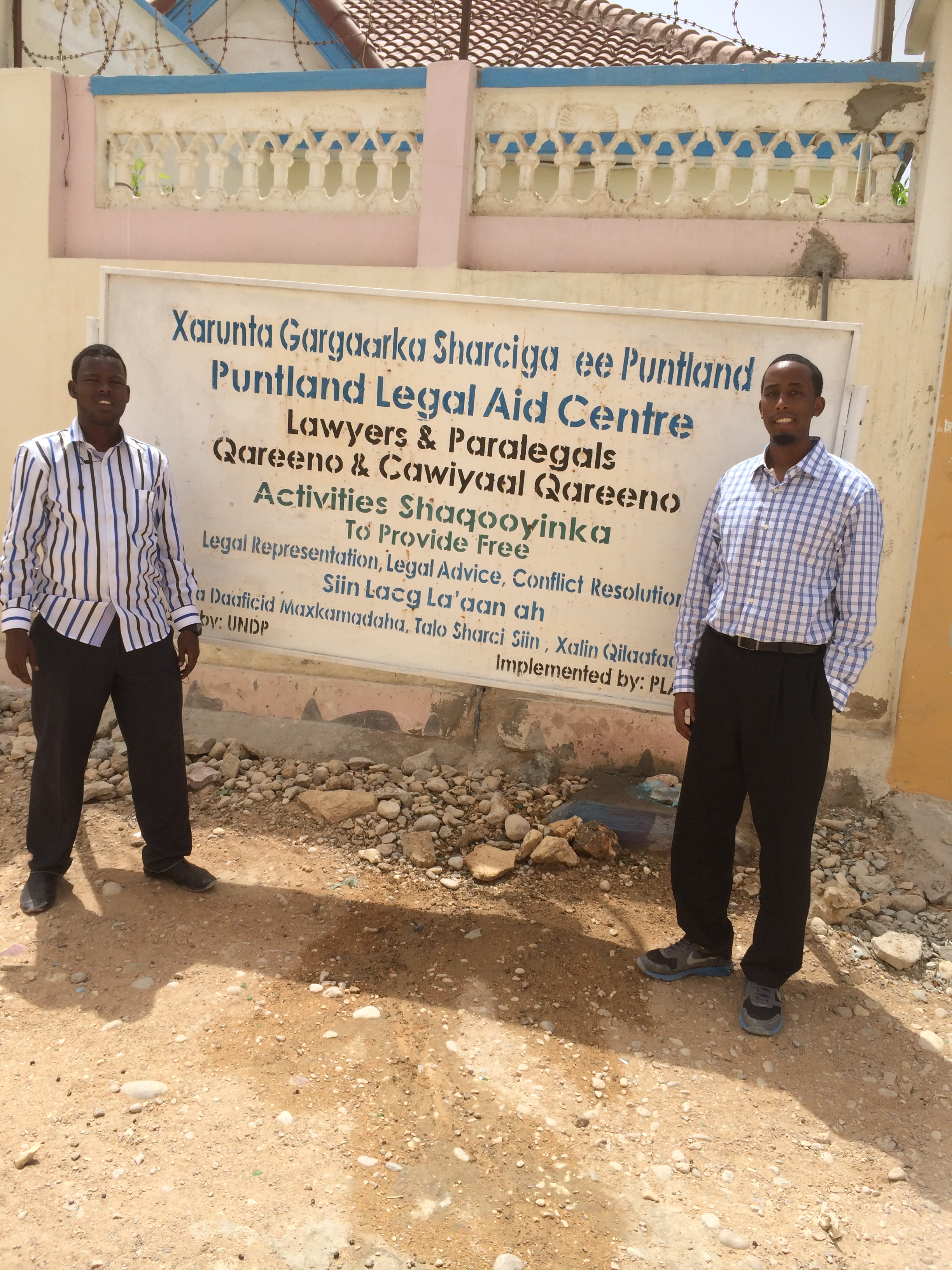 Abadir Barre with Mohamed, a paralegal,  in front of PLAC's office in Bosaso